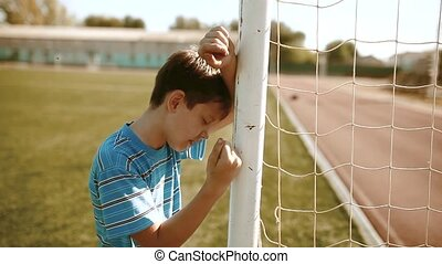 boy teenager soccer football player upset defeat insult sadness and anger. boy teenager grieved after the defeat, well, managed to win. soccer kids concept lifestyle