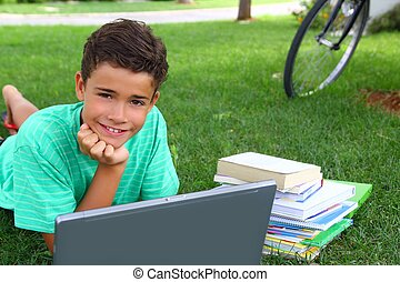 boy teenager homework studying laying green grass garden bycicle background