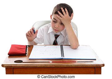 Boy thinkinhg at school desk