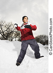 Boy throwing snowball. - Boy standing in snow throwing...