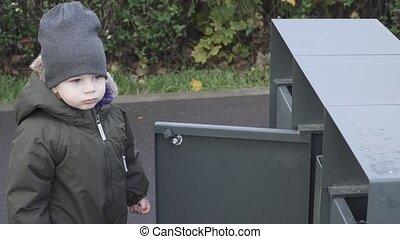 Boy throwing trash in a city park