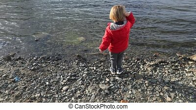 boy throws a stone into the water in the spring