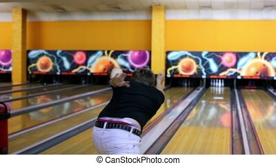 Boy throws bowling ball and then dances happy with result -...