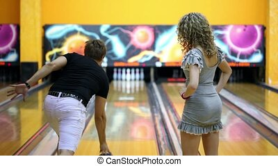 Boy throws bowling ball to beat skittles, girl jumps very...