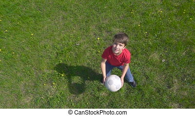 Boy throws up the ball, standing on green lawn