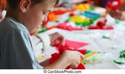 boy together with other children makes flower of color paper