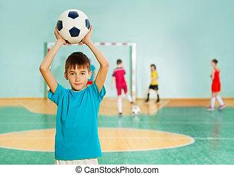Boy tossing soccer ball during football match