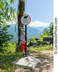 boy traveler is standing near the sign of caution bears