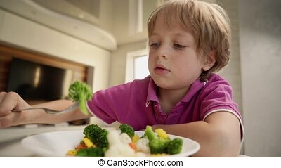 Boy tries to eat a vegetables but dosen't like it and ...