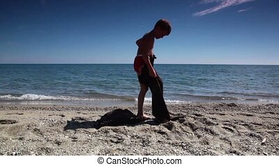 Boy tries to put on pants suit, jacket layed near on beach