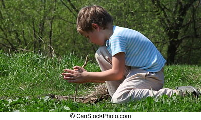Boy tries to take flame by primitive way with stick - boy...