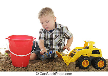 Boy, Truck, Sand and Pail - A young preschooler using his ...