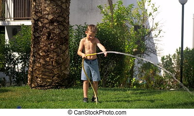Boy trying to cope with water jet when watering lawn - Boy...