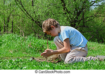 boy trying to take flame by primitive way by stick in wood -...