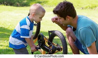Boy trying to turn a wheel