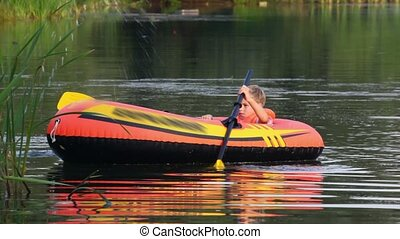 boy turn round on an inflatable boat on lake