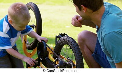 Boy turning a wheel with his father