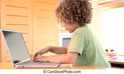 Boy typing on a laptop and waves at the camera