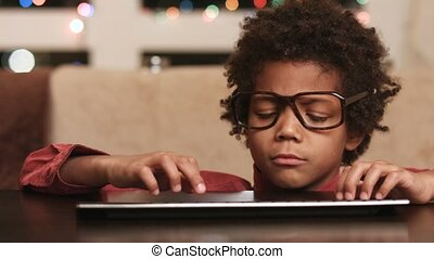 Boy typing on keyboard. Kid in glasses. Ask the internet....