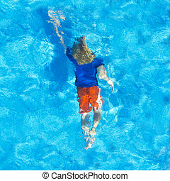 Young child swiming with his clothes on under water, seen from above