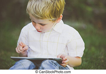 Boy using a computer. - Young boy using a computer tablet.