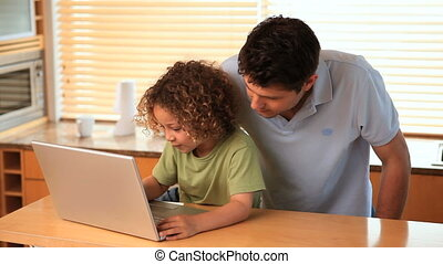 Boy using a laptop with his father