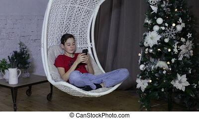 Boy using a smart phone, christmas background