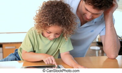 Boy using a tablet computer with his father
