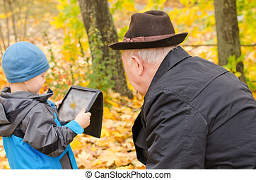 Boy using a tablet pc with grandfather watching