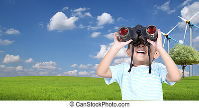 Boy using binoculars with hill and blue sky with clouds in the