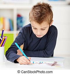 Boy Using Colored Pencil While Drawing On Paper At Table