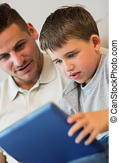 Boy using digital tablet with father