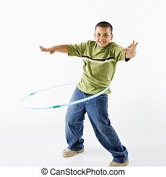 Boy using hula hoop. - Young latino adolescent boy using...