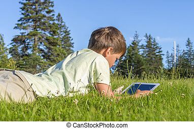 Boy using iPad in the park