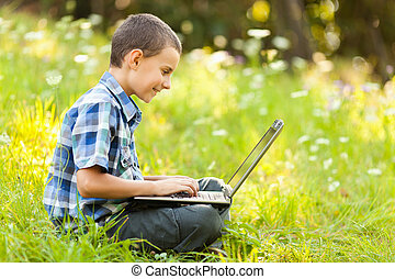 Boy using laptop outdoor