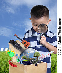 Boy using magnifying glass with toys and globe burst from wooden
