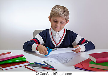 Boy using scissors on the desk