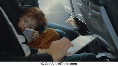 Boy using smart phone and father with tablet in plane
