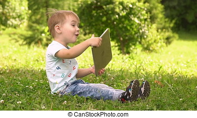 Boy Using Tablet Computer in Park. Slow motion