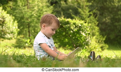 Boy Using Tablet Computer in Park.