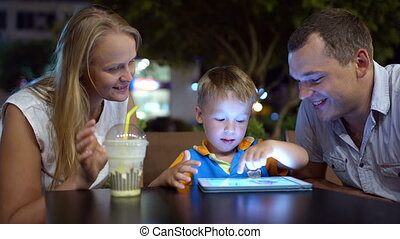 Boy using tablet PC sitting in cafe with parents