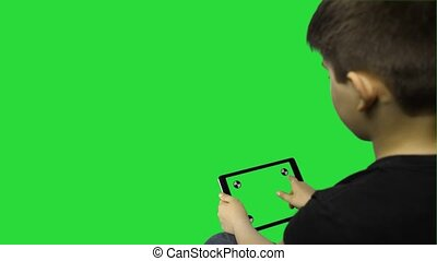 Boy using Tablet  with Green Screen on a green background.horizontally. Easy for tracking and keying  with tracking markers