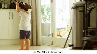 Boy using virtual reality headset in kitchen 4k - Boy using...