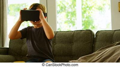 Boy using virtual reality headset on sofa 4k - Boy using...