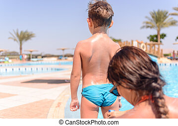 Boy waiting for his mother to apply sunscreen