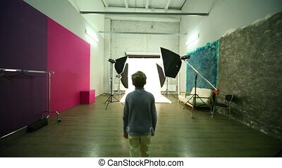 Boy walk across photo studio among spotlights to white...