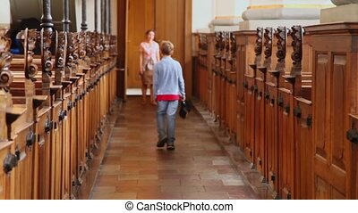 boy walk away in church and mother wait behind - Little boy...