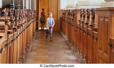 boy walk  in church and mother wait behind