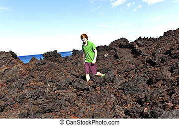boy walking in volcanic area - boy walking on volcanic...