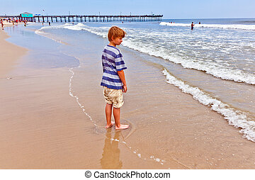 boy walking on the beach with the old beautiful pier